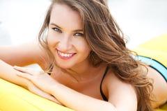 相当明亮的夏天比基尼泳装的少妇在海滩懒人 免版税库存图片