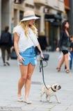 相当有一个哈巴狗的少妇在城市 免版税图库摄影