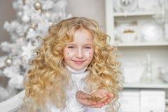 相当有五彩纸屑的白肤金发的小女孩画象在面孔和在圣诞节的手 免版税图库摄影