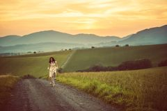 相当有减速火箭的自行车的年轻smilling的妇女在路的日落,葡萄酒往日,减速火箭的样式的女孩在草甸 图库摄影