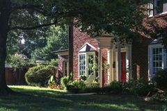 相当有凸出的三面窗的二层的砖房子和从侧角的高大的树木和红色前门看法在与hig的黄昏 免版税库存照片