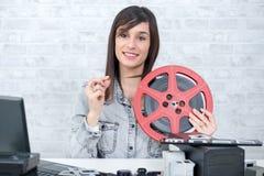 相当有卷轴16mm影片的少妇 免版税库存图片