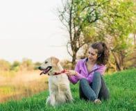 相当有友好的金毛猎犬狗的少妇在步行 免版税库存图片