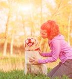 相当有友好的金毛猎犬狗的少妇在步行 图库摄影