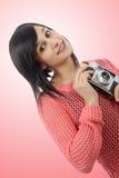 相当有古色古香的照相机的年轻深色的妇女 库存图片