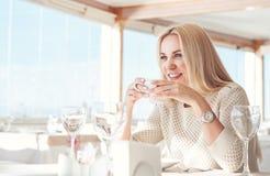 相当有咖啡杯的少妇在晴朗的餐馆 免版税库存图片