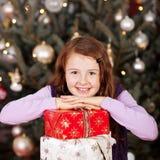相当有她的圣诞节礼物的愉快的女孩 免版税库存图片