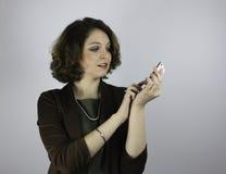 相当有手机的年轻女商人 库存照片