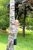 相当有拥抱桦树的花的白肤金发的女孩 免版税库存图片