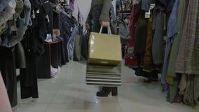 相当有拿着许多购物袋的长的头发的女孩走入商店并且检查衣裳更购物- 股票视频