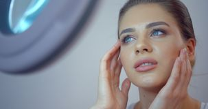 相当有瓷新鲜的皮肤和自然构成的年轻蓝眼睛的女孩是赞赏的她的在镜子的神色 4k英尺长度 影视素材