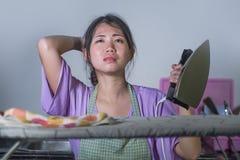 相当有绝望铁工作在家厨房电烙的衣裳的沮丧的年轻人和被注重的亚裔中国妇女和淹没 免版税图库摄影