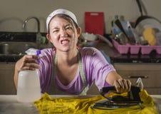 相当有绝望铁工作在家厨房电烙的衣裳的沮丧的年轻人和被注重的亚裔中国妇女和淹没 库存图片