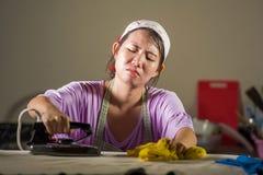相当有绝望铁工作在家厨房电烙的衣裳的沮丧的年轻人和被注重的亚裔中国妇女和淹没 免版税库存图片