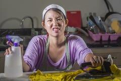 相当有绝望铁工作在家厨房电烙的衣裳的沮丧的年轻人和被注重的亚裔中国妇女和淹没 库存照片