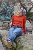 相当有编织盖帽的白肤金发的妇女在公园坐岩石 免版税库存照片