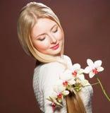 相当有美丽的头发和花兰花的年轻白肤金发的妇女 免版税库存照片