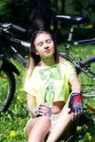 相当有自行车的少妇画象在室外的公园- 女孩坐草和饮料从a浇灌 免版税库存照片