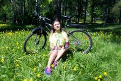 相当有自行车的少妇画象在室外的公园- 女孩坐草和饮料从a浇灌 图库摄影