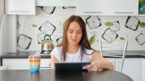 相当有茶的少妇使用数字式片剂的在轻的舒适厨房 股票录像