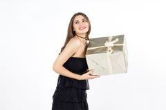 相当有金黄当前箱子的少妇微笑并且笑 免版税图库摄影