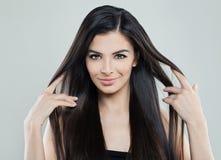 相当有长的柔滑的头发的年轻式样妇女 免版税库存照片