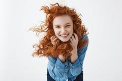 相当有飞行的卷发微笑的笑快乐的红头发人女孩看在白色背景的照相机 免版税库存图片
