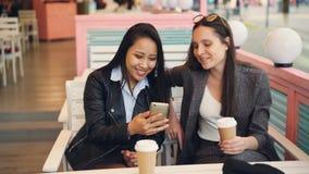 相当朋友使用坐现代的智能手机在桌在咖啡馆与的小姐拿走咖啡 愉快的女孩是 股票录像