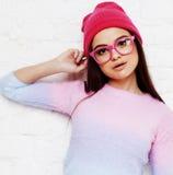 相当桃红色玻璃和帽子情感摆在的愉快微笑的,生活方式人概念年轻十几岁的女孩行家 免版税图库摄影