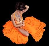 橙色服装的性感的东方舞蹈家 免版税库存照片