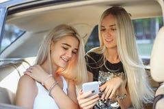 相当欧洲女孩在汽车的25-30岁在手机做照片 免版税库存图片
