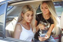 相当欧洲女孩在汽车的25-30岁在手机做照片 免版税图库摄影
