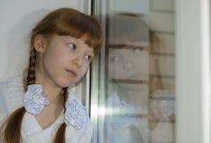 相当沉思女孩看在窗口特写镜头外面 库存图片