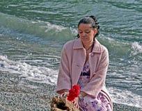 相当海滩的多种族妇女在桃红色外套 库存照片