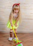 相当清洗房子的小白肤金发的女孩 免版税库存图片