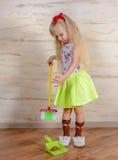 相当清洗房子的小白肤金发的女孩 免版税库存照片