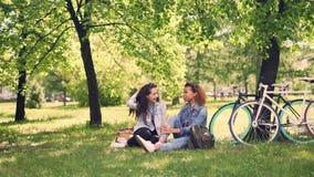 相当白种人女孩与她非裔美国人的朋友谈话并且笑在断裂期间在骑自行车以后,年轻 影视素材