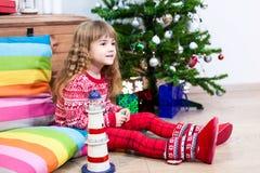 相当白种人女孩坐枕头在圣诞前夕、红色毛线衣和毛皮botos 免版税库存图片