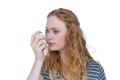 相当白肤金发使用哮喘吸入器 免版税库存图片