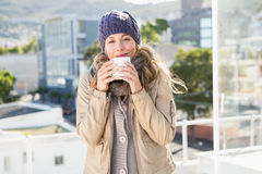 相当白肤金发在喝热的饮料的温暖的衣裳 图库摄影
