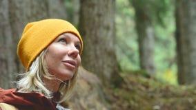 相当白肤金发在有背包的一个黄色帽子在一个女孩旅客的一张具球果森林画象看慢的 股票视频