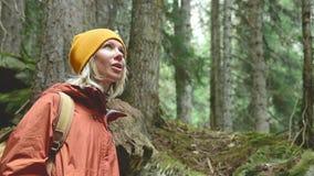 相当白肤金发在有背包的一个黄色帽子在一个女孩旅客的一张具球果森林画象看慢的 影视素材