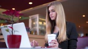 相当白肤金发在黑夹克在咖啡馆商店坐 她喝她的咖啡并且与笔记本一起使用 股票视频