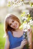 相当白肤金发摆在开花的灌木附近 免版税图库摄影