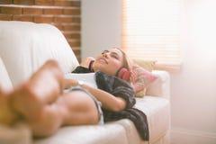相当白肤金发放松在听到音乐的长沙发 免版税图库摄影