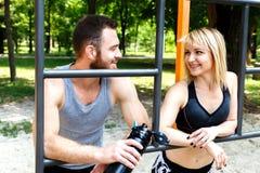 相当白肤金发的休息在锻炼trainin以后的女孩和有胡子的人 免版税库存图片