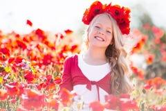 相当白肤金发的儿童女孩在鸦片草甸佩带从红色花的花圈 免版税图库摄影