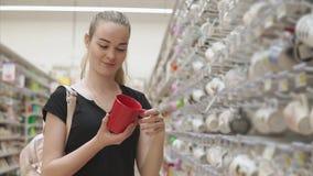 相当白肤金发的女孩从机架得到在一家商店每红色陶瓷杯子,看 股票录像