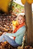 相当白肤金发的女孩在秋天公园坐 免版税图库摄影