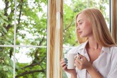 相当白肤金发的女孩是松弛在窗台 免版税库存照片